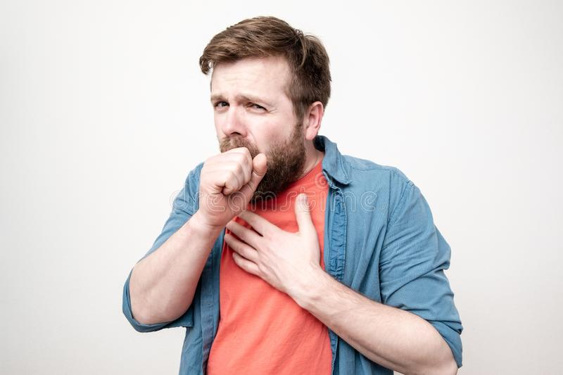 Человек-медведь кашляет, закрывает рот одной рукой, а другой прижимается к груди на белом фоне. стоковое фото