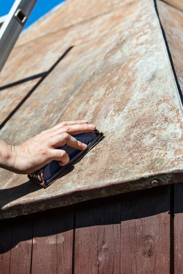 Человек меля крыша сарая сада с зашкурить блоком, Русью стоковая фотография rf