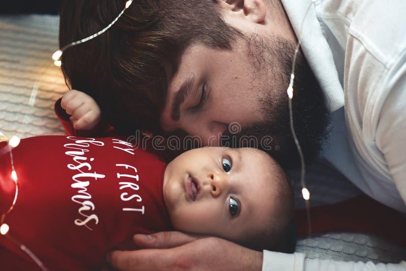 человек младенца Молодой мышечный младенец удерживания человека и целовать ее стоковые изображения
