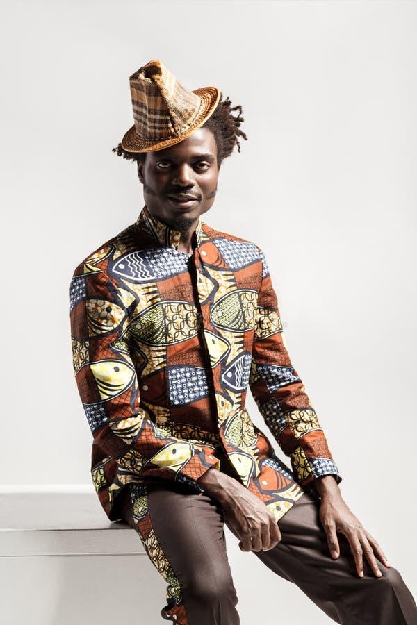 Человек моды счастья африканский смотря камеру и сидит стоковое фото rf