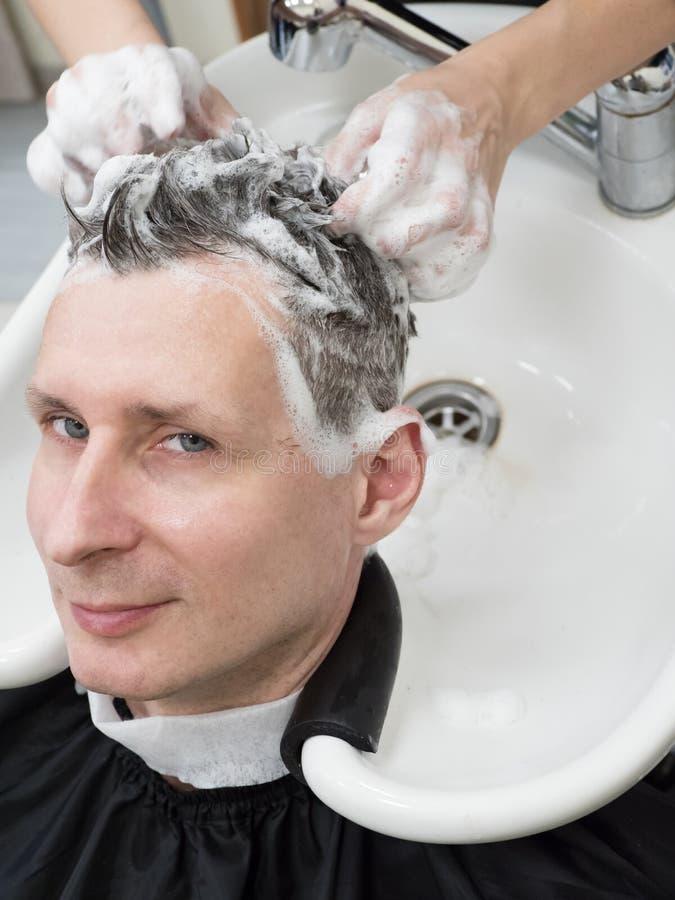Человек моет его волосы после стрижки стоковое изображение rf
