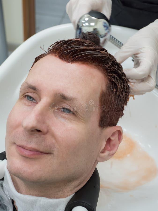 Человек моет краску с волосами стоковые изображения