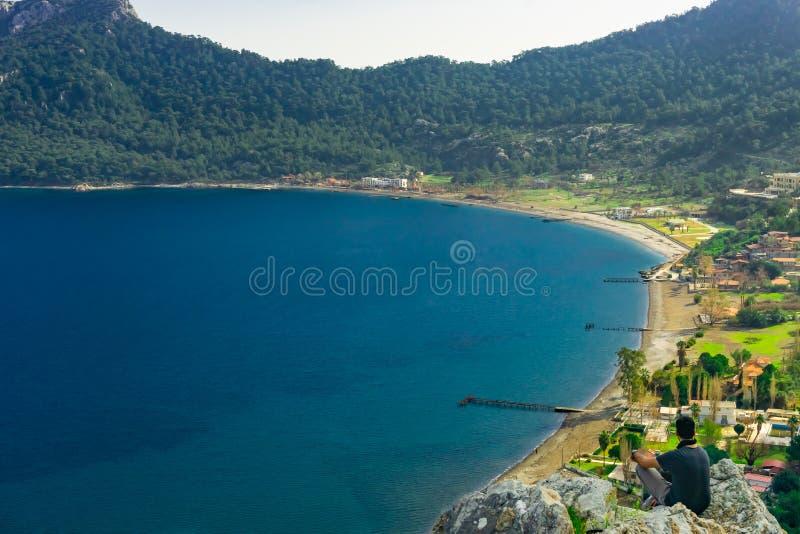 Человек наблюдая взгляд залива Marmaris Изумляя ландшафт с горой, пляжем и деталью залива Kumlubuk, Marmaris, Турция стоковые фотографии rf