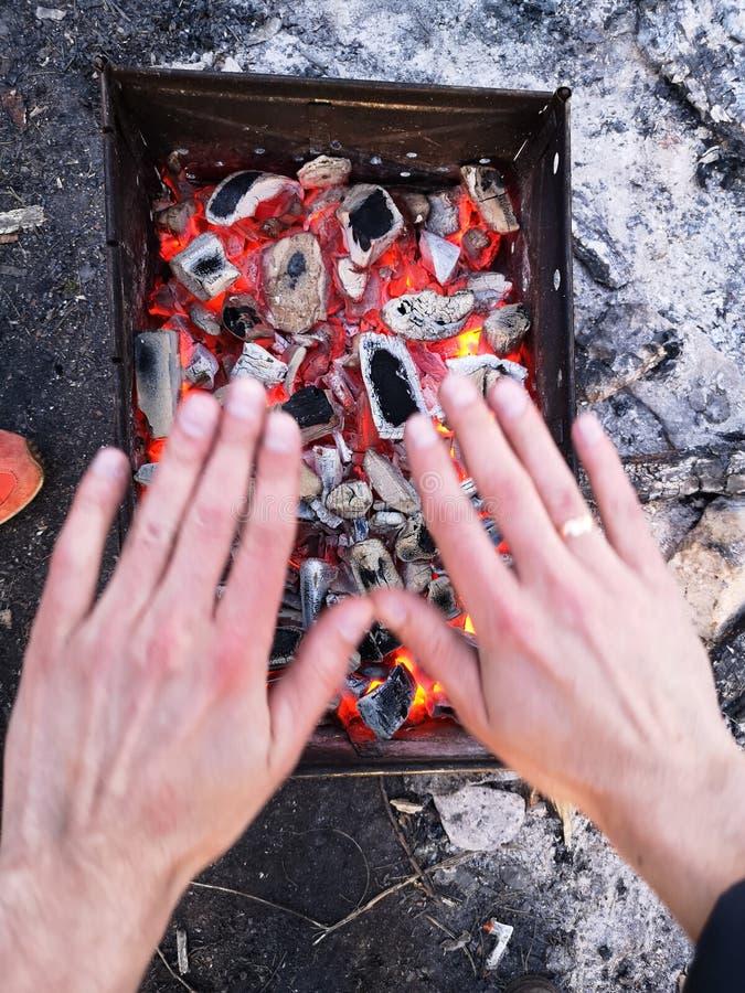 Человек нагревает его руки перед открытым огнем Располагаясь лагерем концепция с на открытом воздухе открытыми пламенами огня Тур стоковая фотография rf
