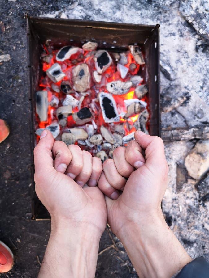 Человек нагревает его руки перед открытым огнем Располагаясь лагерем концепция с на открытом воздухе открытыми пламенами огня Тур стоковые изображения rf