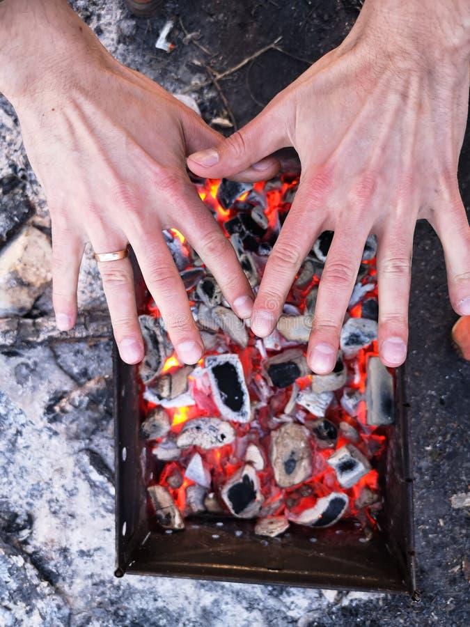 Человек нагревает его руки перед открытым огнем Располагаясь лагерем концепция с на открытом воздухе открытыми пламенами огня Тур стоковые фотографии rf