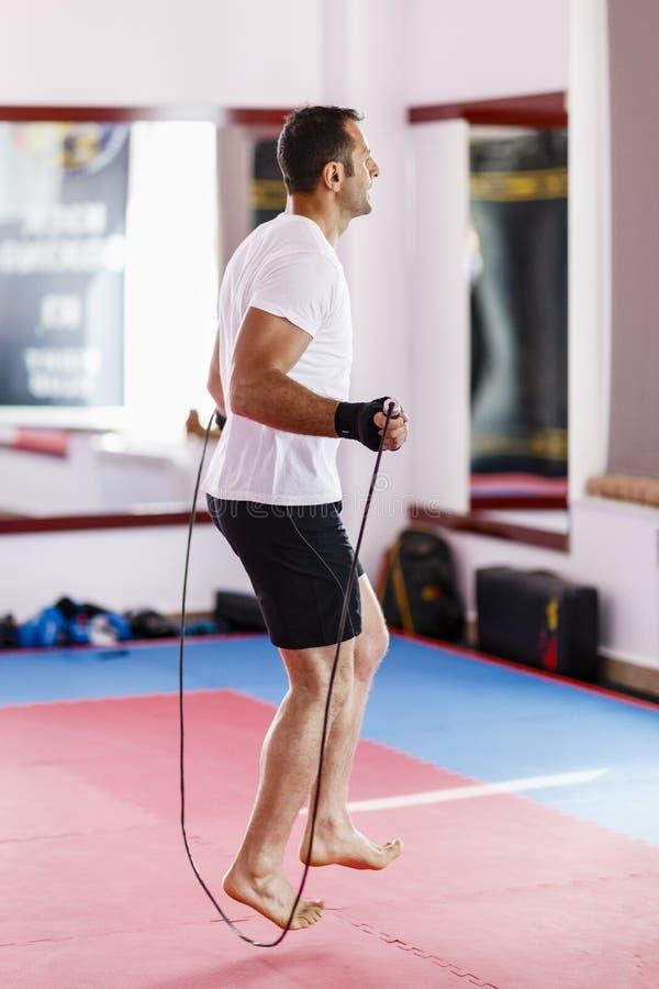Человек нагревает с скача веревочкой в спортзале стоковая фотография rf