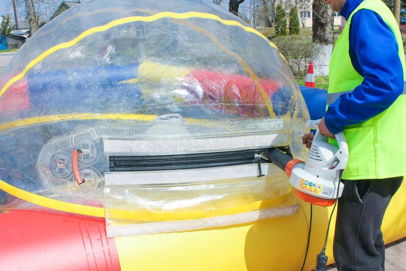 Человек надувает большой воздушный шар для езд воды Впрыска  стоковое фото rf