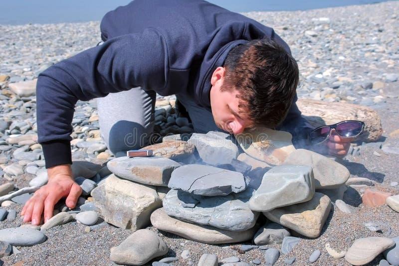 Человек надувает угли дуя на огне на пляже камня моря Делать костер кампуса стоковые фотографии rf