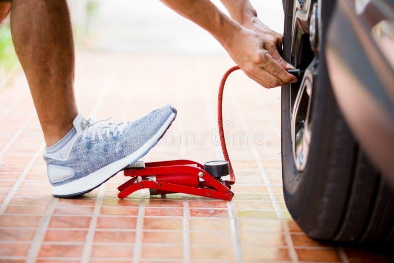 Человек надувая покрышку автомобиля с ножным насосом, человеком положил белые ботинки спорта надувая покрышку автомобиля с красны стоковые изображения rf