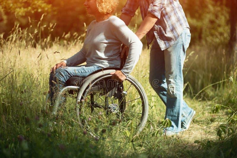 Человек нажимает кресло-коляску с его девушкой, стоковое фото rf