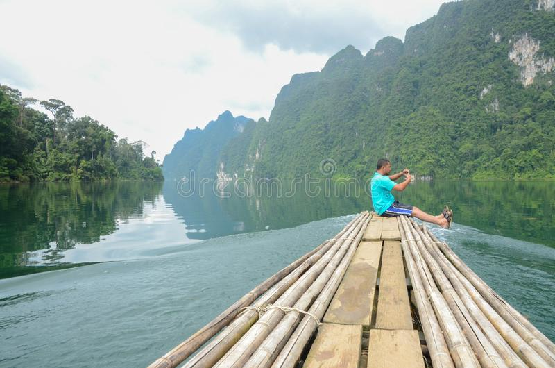 Человек наслаждается взглядом ландшафта красивой природы сценарным на бамбуковой шлюпке на национальном парке Khao Sok который пр стоковые изображения rf