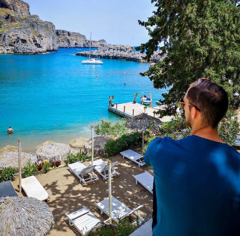 Человек наслаждается волшебным морем этого острова конечный пункт назначения на каникулы в исторической деревне стоковая фотография rf