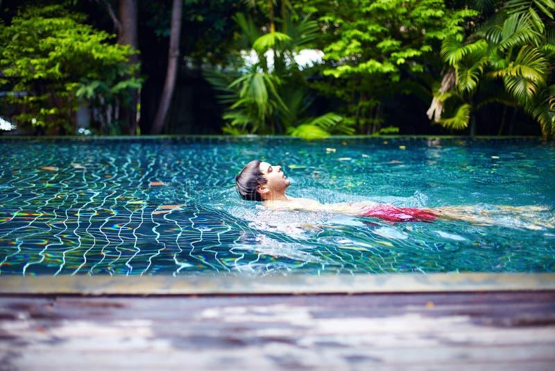 Человек наслаждается поплавать в бассейне на тихом избежании убежища стоковые фотографии rf