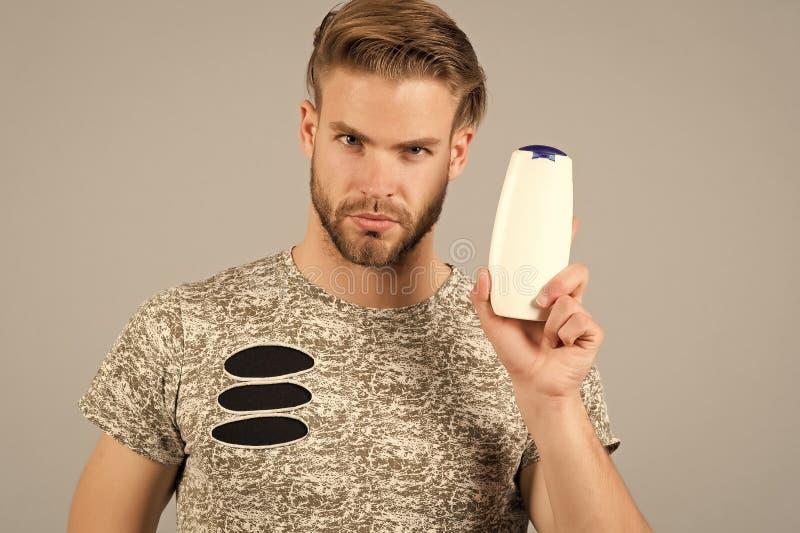 Человек наслаждается свежестью после мыть волосы с шампунем Гай с стилем причёсок держит шампунь бутылки, космос экземпляра Уход  стоковая фотография rf