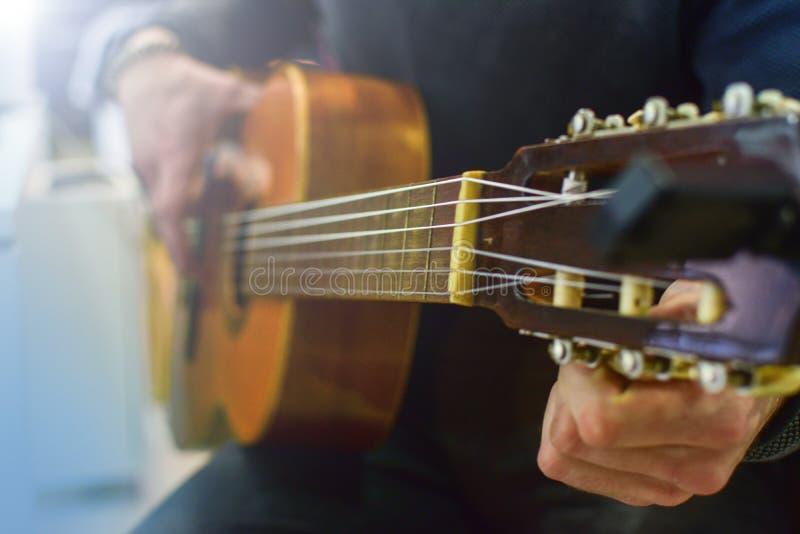 Человек настраивая акустическую испанскую гитару Урок гитары игры стоковое изображение rf