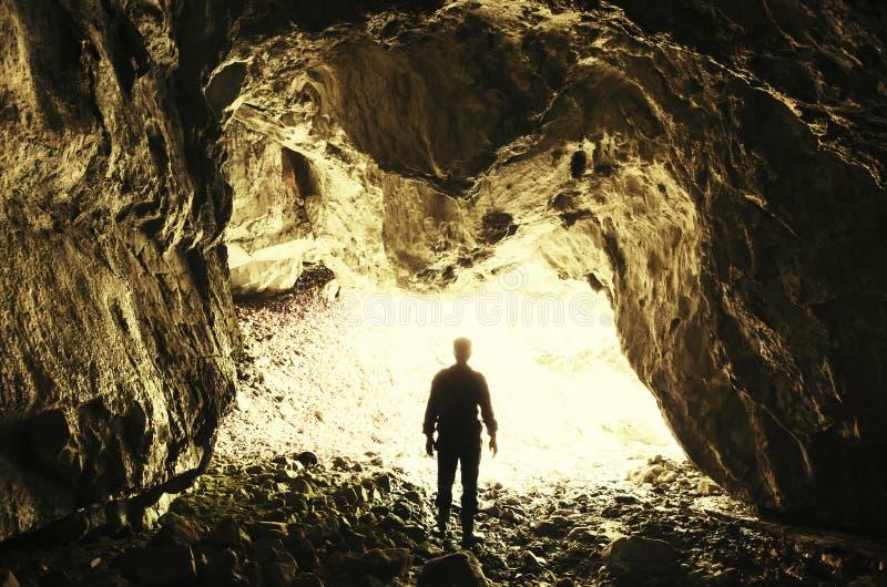 Человек на входе пещеры с ярким светом стоковая фотография rf