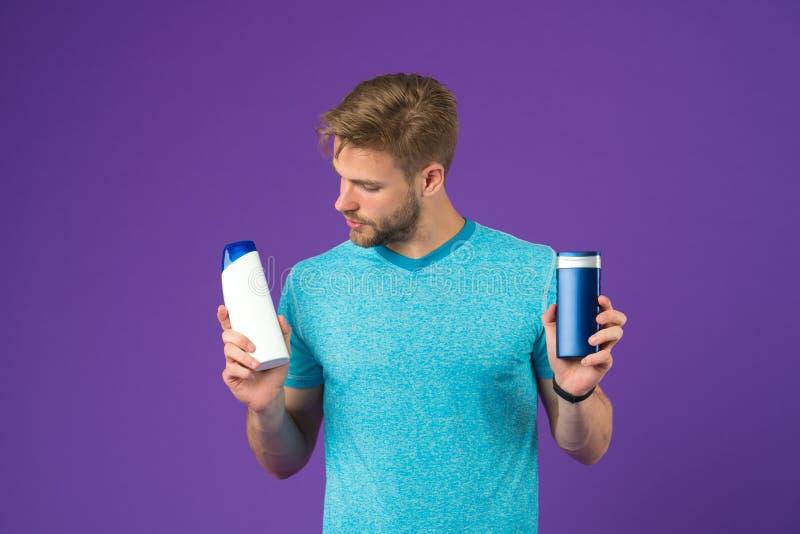 Человек на заботливой стороне выбирает шампунь, фиолетовую предпосылку Гай с щетинкой держит 2 бутылки с шампунем, космосом экзем стоковая фотография