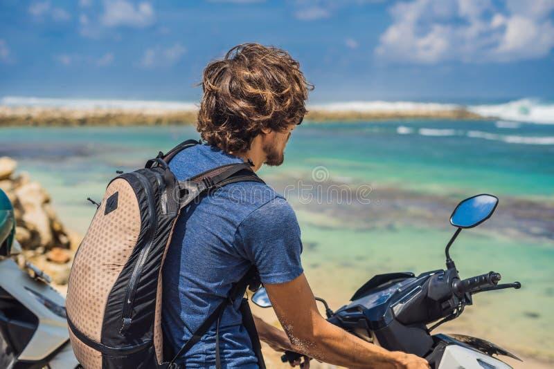 Человек на мопеде, мотоцикле восхищает красивое море стоковые фотографии rf