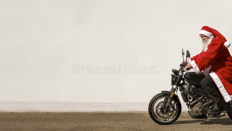 Человек на мотоцилк в типичном костюме Санта Клауса стоковое изображение rf