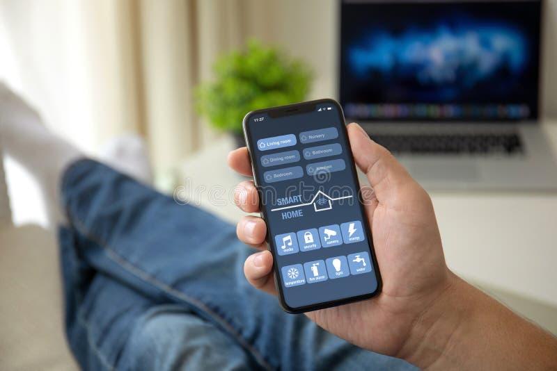 Человек на софе держа телефон с главным экраном app умным