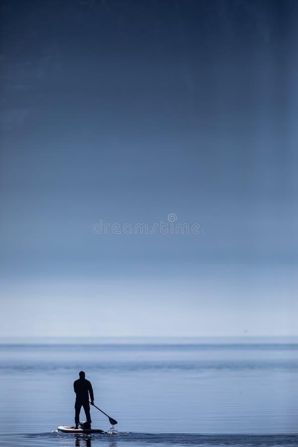 Человек на стойки доске padlle вверх стоковое фото