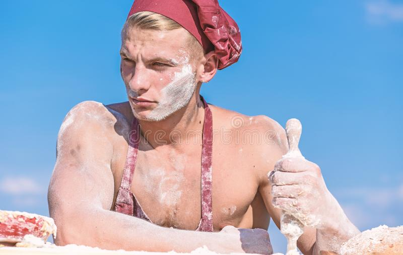 Человек на строгой стороне носит варить шляпу и рисберму, небо на предпосылке Концепция шеф-повара Кашевар с сексуальным торсом д стоковая фотография