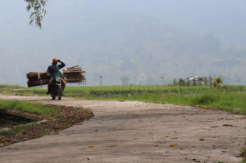 Человек на швырке нося мотоцикла стоковые изображения