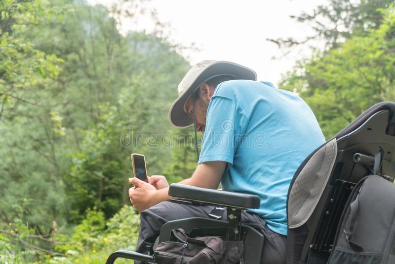 Человек на электрической кресло-коляске используя камеру смартфона в природе стоковое фото