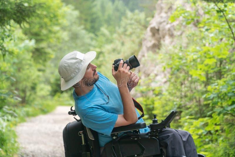 Человек на электрической кресло-коляске используя mirrorless природу камеры, наслаждаясь свободой и делая искусство стоковые изображения