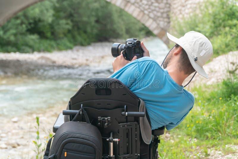 Человек на электрической кресло-коляске используя mirrorless природу камеры, наслаждаясь свободой и делая искусство стоковые изображения rf