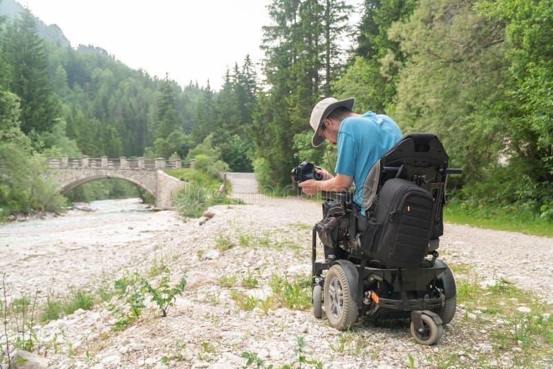 Человек на электрической кресло-коляске используя mirrorless природу камеры, наслаждаясь свободой и делая искусство стоковое фото