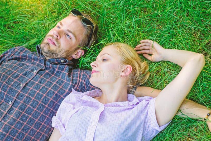 Человек небритый и девушка кладут на луг травы более близкая природа к Беспечальные Гая и девушки счастливые наслаждаются свежест стоковое фото rf