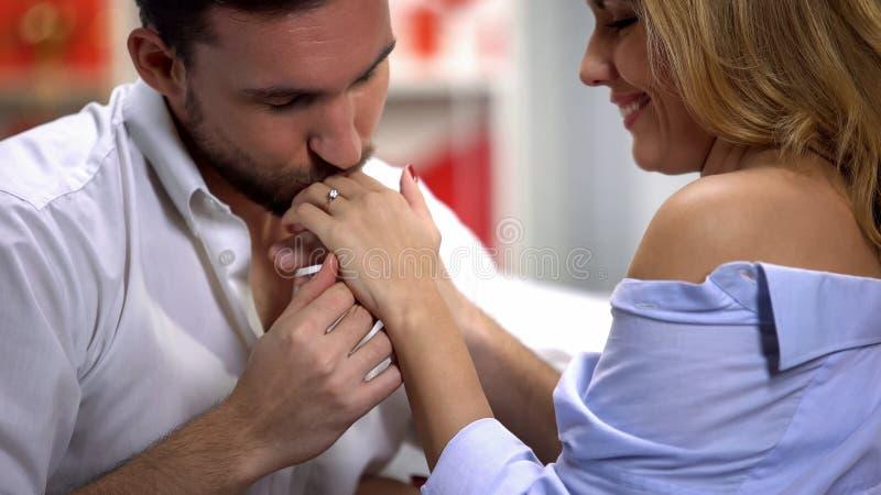 Человек нежно целуя руку женщины с обручальным кольцом, замужеством предложения, любовью стоковые фото