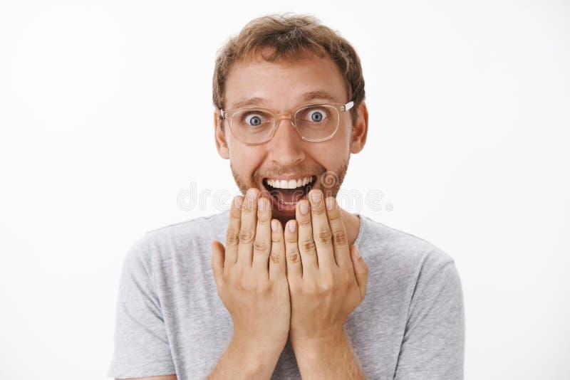 Человек не может спрятать счастье и ободрение получая внушительные новости держа ладони над ртом усмехаясь широко с стоковое фото
