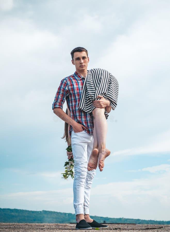 Человек носит девушку на небе Внешний идти уставший после выматывать день Пешее перемещение соедините влюбленность детеныши пар стоковая фотография