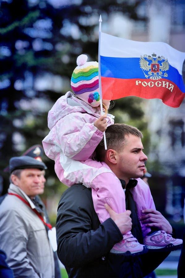 Человек носит ребенка на его плечах и русском флаге стоковая фотография rf