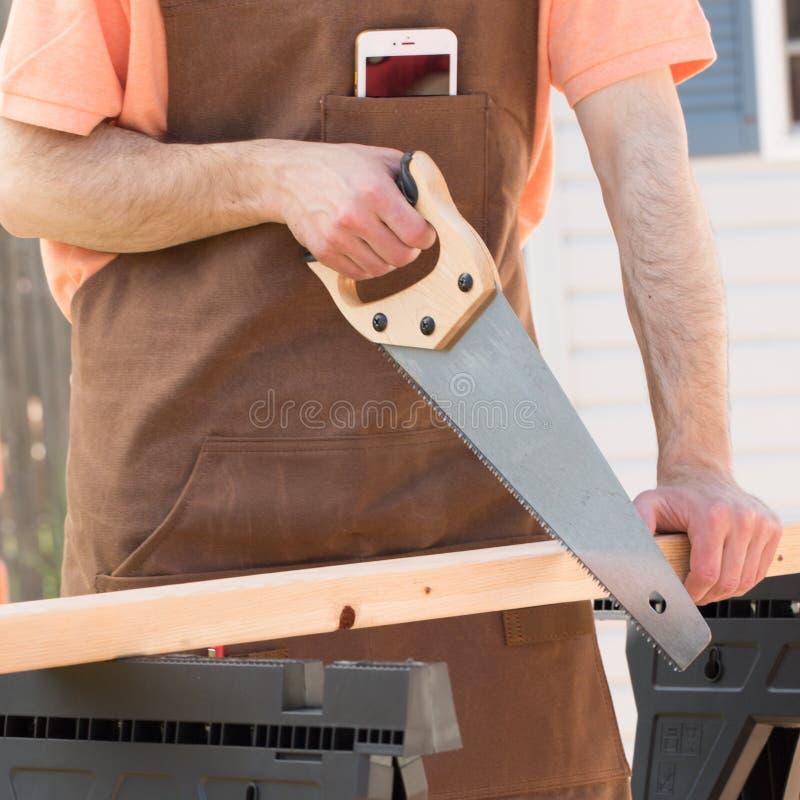 Человек нося рисберму Брауна и пиля древесину стоковые изображения