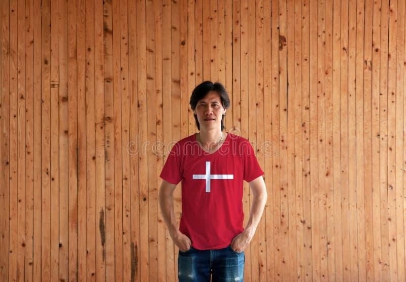 Человек нося рубашку цвета флага Дании и стоя с 2 руками в карманах тяжелого дыхания на деревянной предпосылке стены стоковые фото