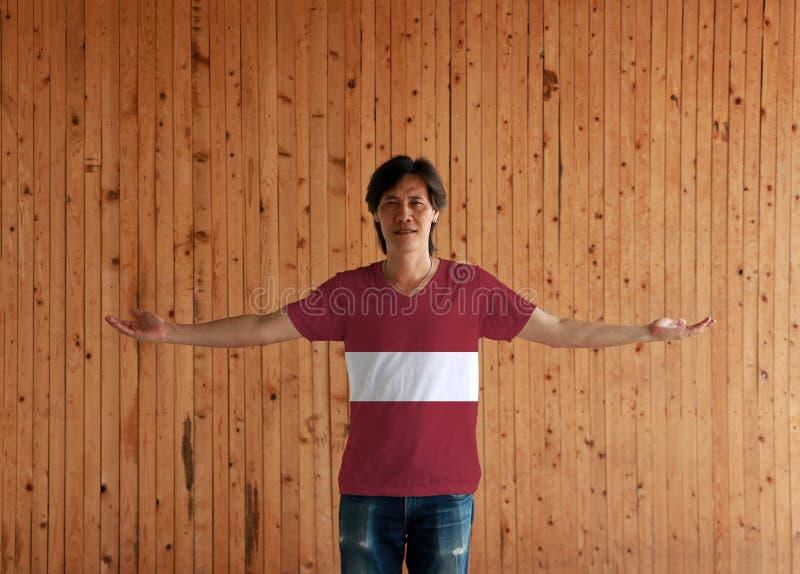 Человек нося рубашку цвета флага Латвии и стоя с оружиями широко открытыми на деревянной предпосылке стены стоковые фото