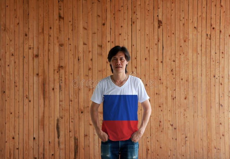 Человек нося рубашку цвета флага России и стоя с 2 руками в карманах тяжелого дыхания на деревянной предпосылке стены стоковые фотографии rf