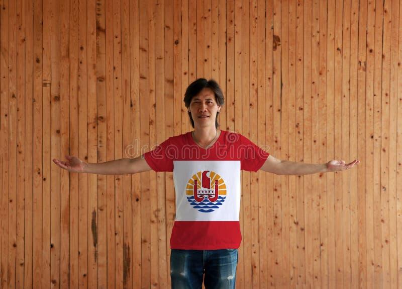 Человек нося рубашку цвета флага Французской Полинезии и стоя с оружиями широко открытыми на деревянной предпосылке стены стоковое изображение rf