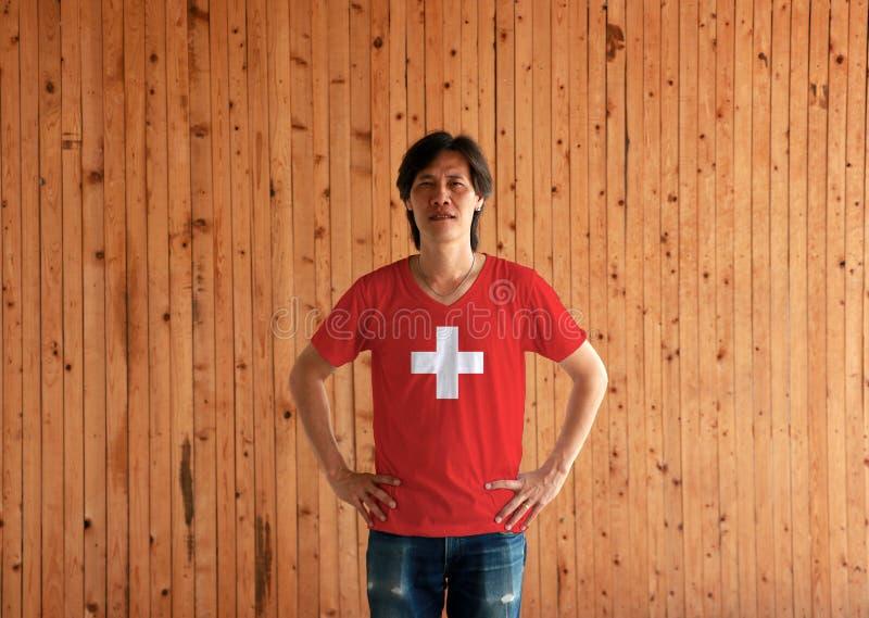 Человек нося рубашку цвета флага Швейцарии и стоя с подбоченясь на деревянной предпосылке стены стоковое изображение rf
