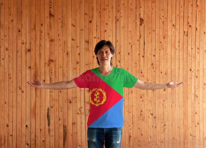 Человек нося рубашку цвета флага Эритреи и стоя с оружиями широко открытыми на деревянной предпосылке стены стоковые изображения rf