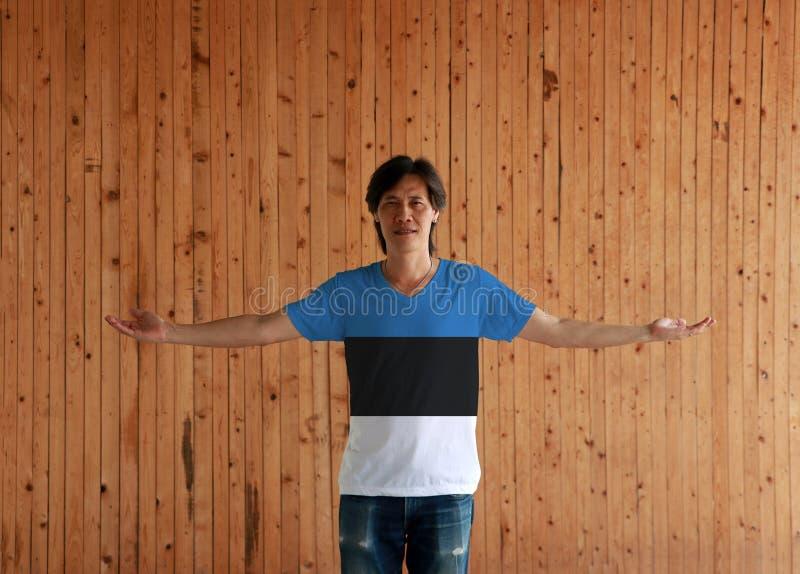 Человек нося рубашку цвета флага Эстонии и стоя с оружиями широко открытыми на деревянной предпосылке стены стоковые фото