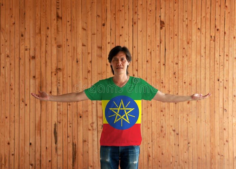 Человек нося рубашку цвета флага Эфиопии и стоя с оружиями широко открытыми на деревянной предпосылке стены стоковое фото rf