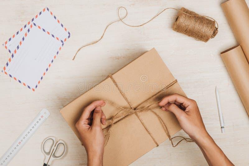 Человек оборачивая подарок Пакет обернутый в коричневой бумаге и связанный с стоковые изображения rf
