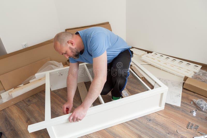 Человек одел вскользь собирая мебель в новом доме Ремонт плотника и собирая мебель дома стоковое изображение rf