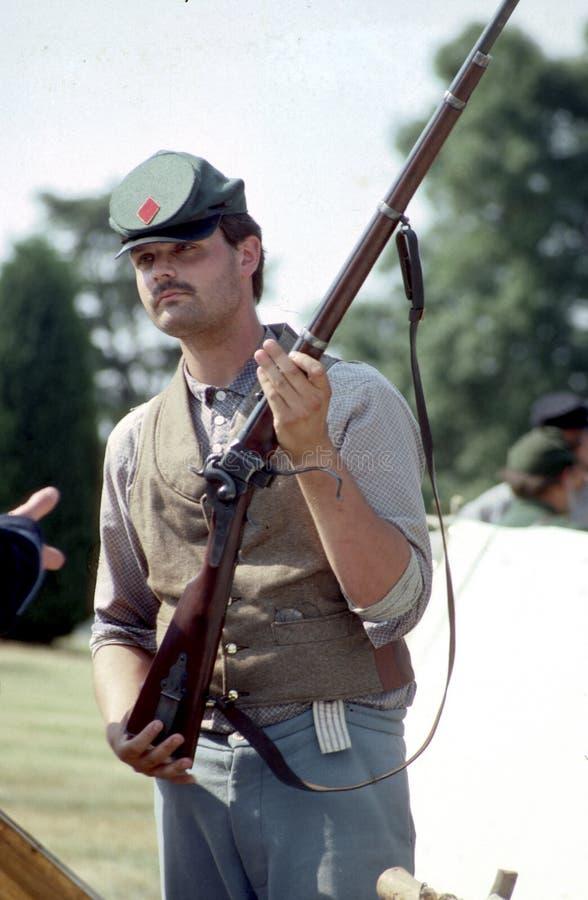Человек одетый как солдат гражданской войны с мушкетом во время reenactment стоковое фото rf