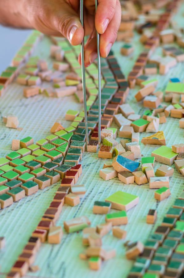 Человек организует с щипчики головоломка керамических элементов для конструкции керамических художественных произведений Мозаика  стоковые изображения